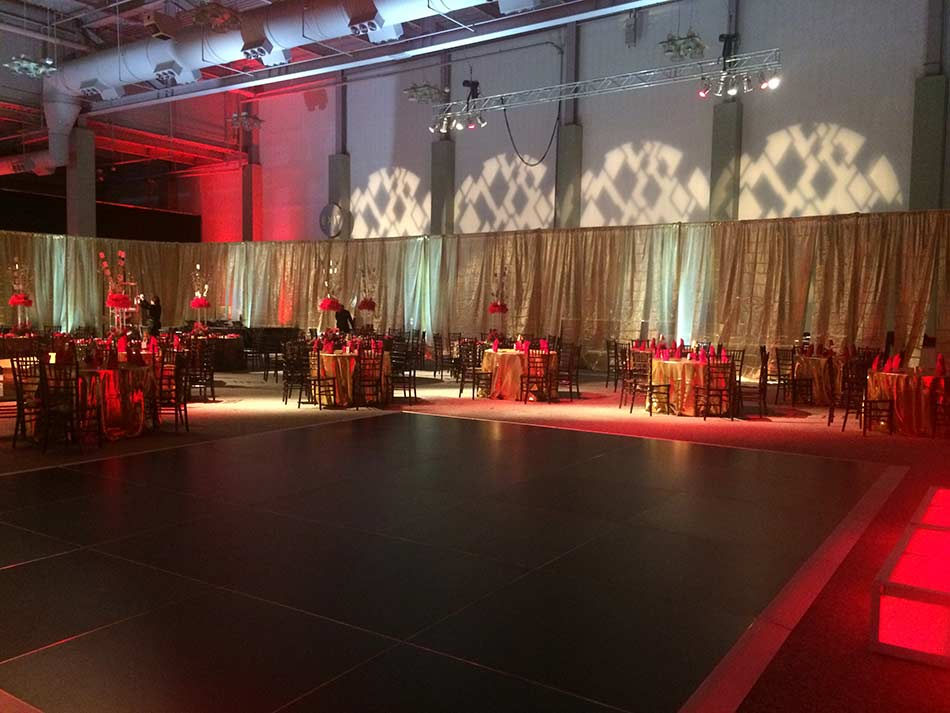 Gold-lame-draping-with-black-dance-floor-video-projection-and-gold-red-table-linens