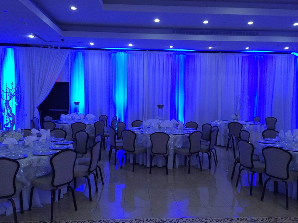 Pipe-and-drape-with-low-heat-lighting-sparkle-tablecloths-and-classic-seating