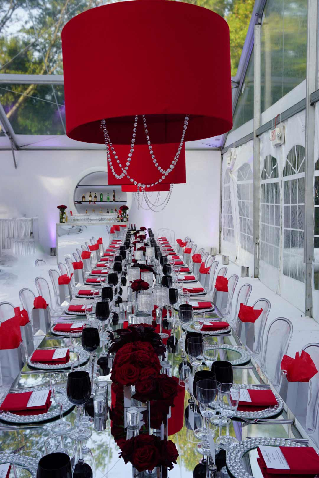 mirrored-table-for-event-rental-with-red-accessories-and-red-lampshade-chandelier